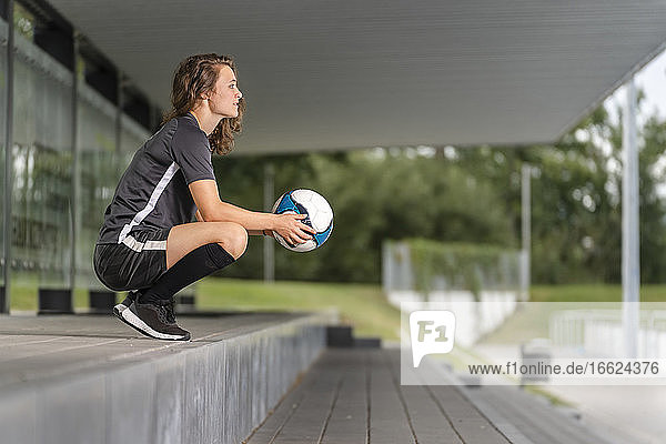 Thoughtful female player holding soccer ball while crouching on steps