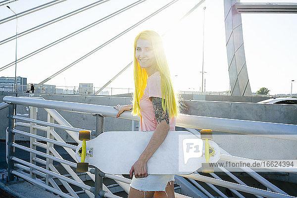 Frau mit Skateboard auf einer Brücke an einem sonnigen Tag Frau mit Skateboard auf einer Brücke an einem sonnigen Tag