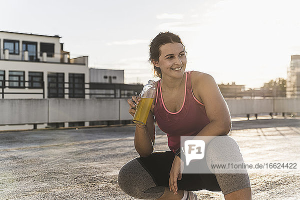 Smiling young woman holding drink while crouching on terrace during sunset