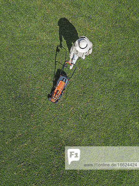 Woman with lawn mower standing on grass