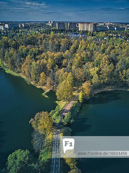 Bridge over pond by green trees at Skitsky Ponds park near city against sky