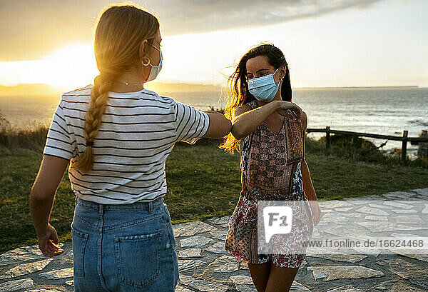Female friends in protective face masks elbow bumping on footpath during COVID-19 outbreak