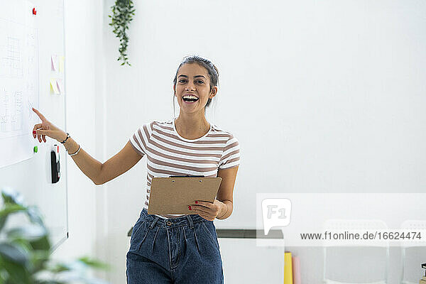Cheerful female architect pointing at whiteboard while holding clipboard in creative workplace