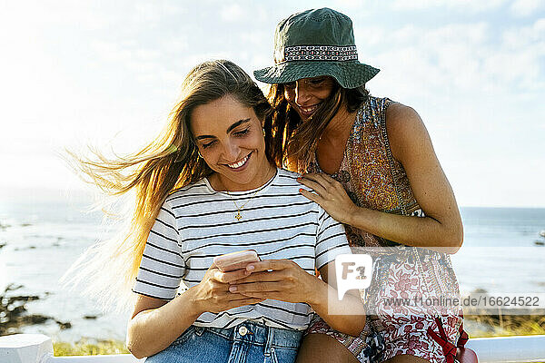 Smiling young female friends using smart phone against sea during sunny day