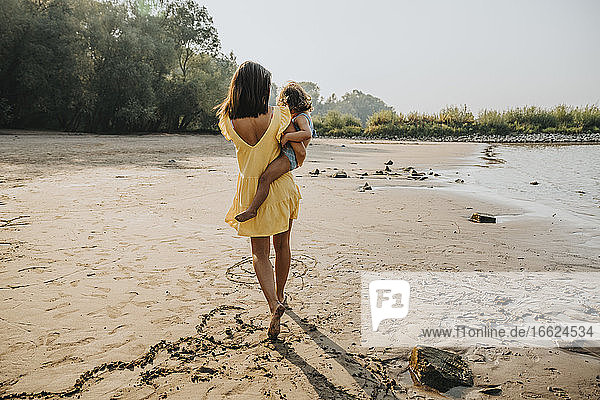 Mother carrying daughter while walking on sand at beach