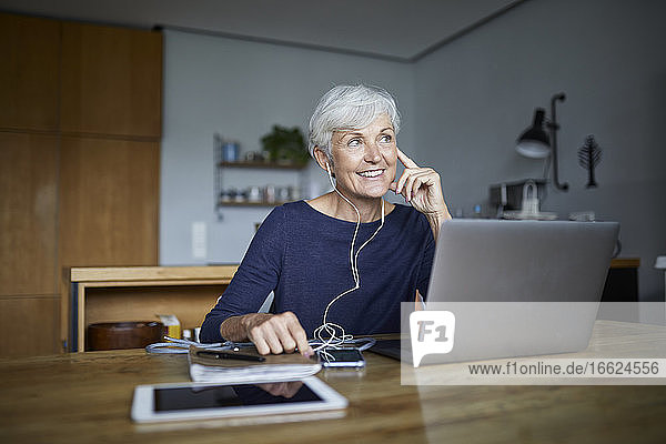 Contemplating woman listening to music on smart phone and using laptop while sitting at home