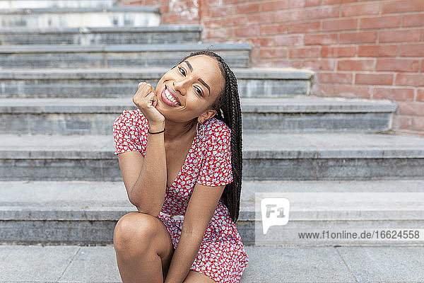 Smiling woman with hand on chin sitting on staircase in city