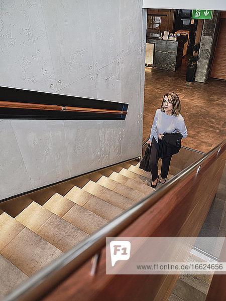 Ältere Frau beim Treppensteigen im Hotel Ältere Frau beim Treppensteigen im Hotel