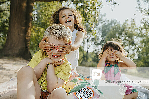 Cute kids covering eyes while sitting at beach on sunny day