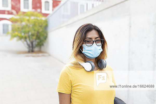 Young woman wearing protective mask and eyeglasses at bus stop