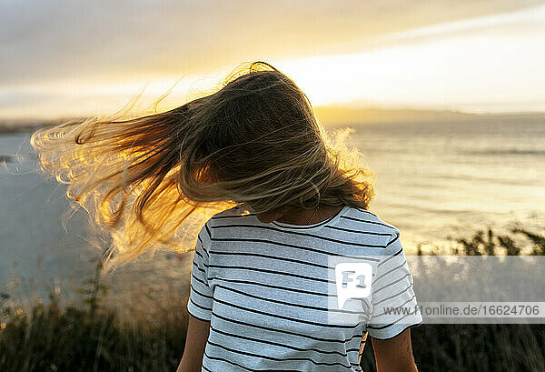 Young woman tossing hair against cloudy sky during sunset
