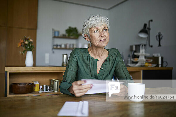 Senior woman reading letter looking away while sitting at home