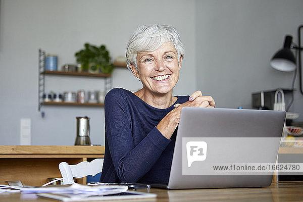 Smiling active senior using laptop while sitting at home