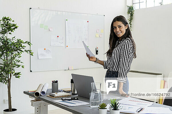 Smiling beautiful businesswoman holding plan while standing at desk in creative office