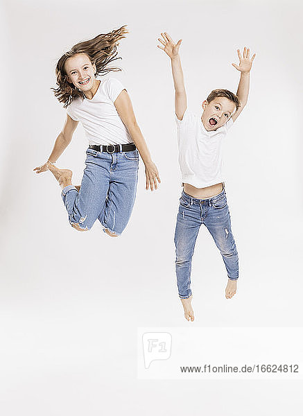 Cheerful siblings jumping against white background