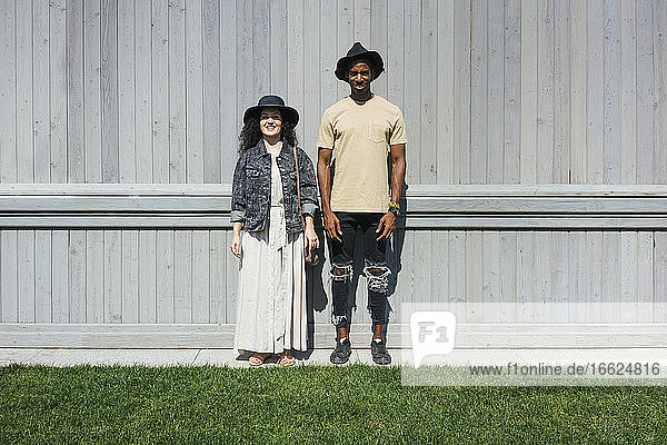 Man and woman wearing hat standing against wall