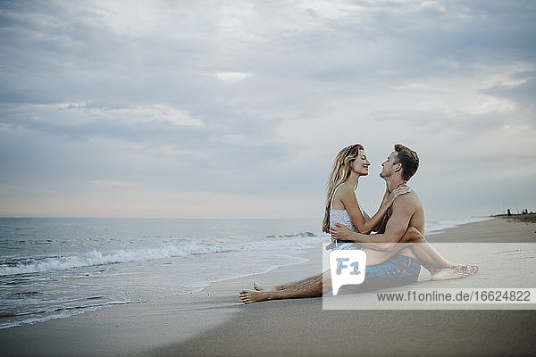 Junges Paar schaut sich am Strand sitzend an