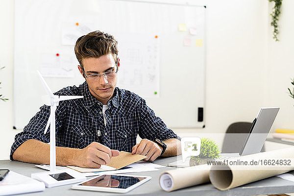 Young man writing while working by desk at office
