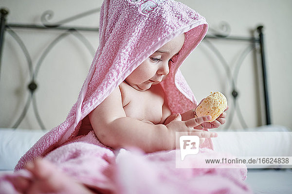 Baby girl in pink towel playing bath sponge while sitting on bed in bedroom