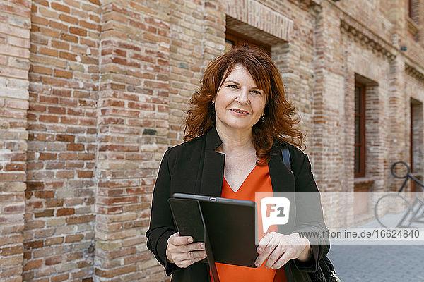 Lächelnde Frau  die ein digitales Tablet hält  während sie an einem Gebäude in der Stadt steht Lächelnde Frau, die ein digitales Tablet hält, während sie an einem Gebäude in der Stadt steht
