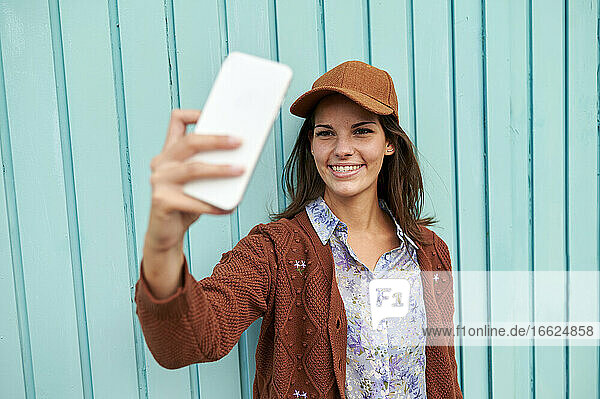 Junge Frau lächelnd während der Einnahme selfie gegen blaue Metalltür Junge Frau lächelnd während der Einnahme selfie gegen blaue Metalltür