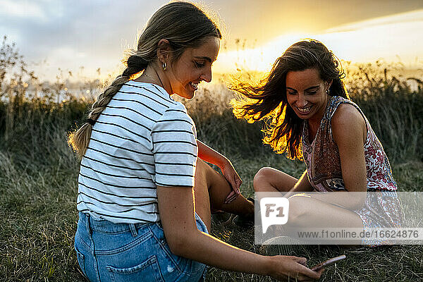 Smiling young woman showing smart phone to female friend while sitting on field during sunset