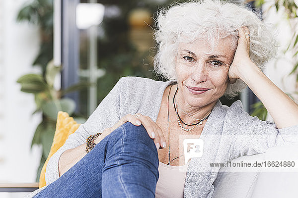 Smiling mature woman with hands in hair looking away while sitting at home