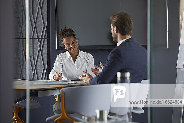 Businessman and colleague discussing while sitting in office