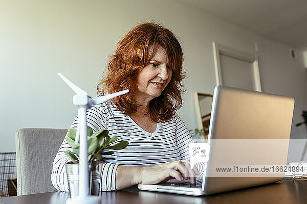 Smiling woman working on laptop while sitting by table at home