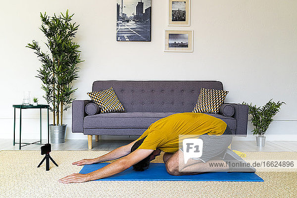 Fitness trainer with tripod and mobile phone kneeling while exercising at home