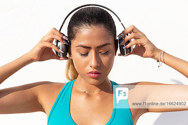 Beautiful young woman wearing headphones before exercising against white wall on sunny day