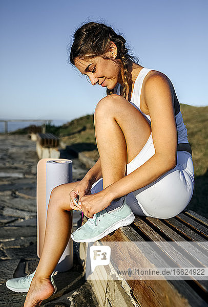 Smiling young woman tying shoelace while sitting on seat against clear sky at sunset