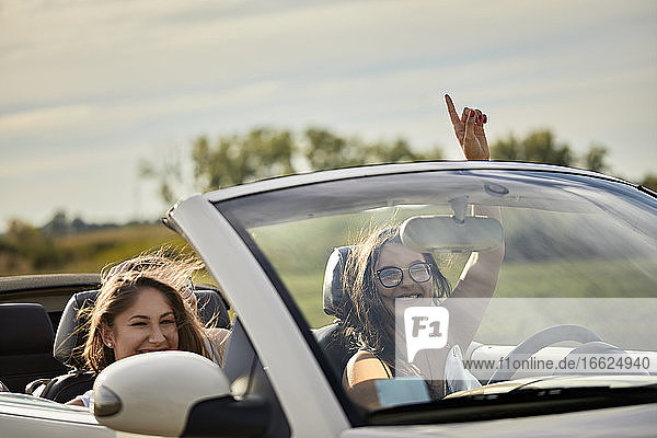 Cheerful female friends enjoying road trip in convertible against sky at sunset