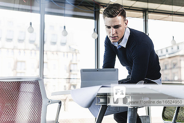 Male professional working over digital tablet while sitting on desk in office