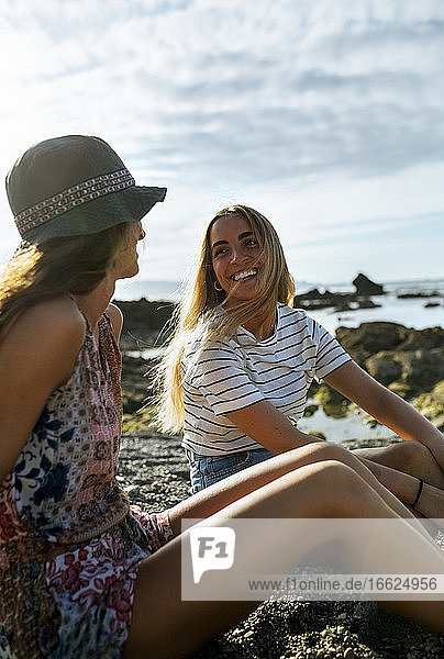 Cheerful young female friends sitting at beach during sunny day