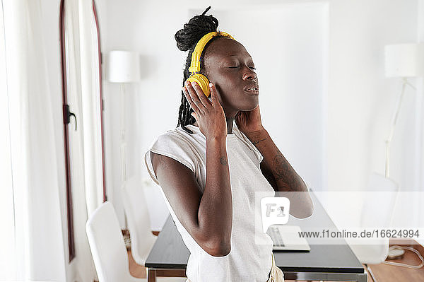 Young woman with eyes closed listening music while standing at home