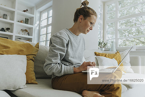 Mid adult woman working on laptop while sitting on sofa at home