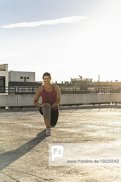 Smiling young woman exercising on building terrace against sky on sunny day