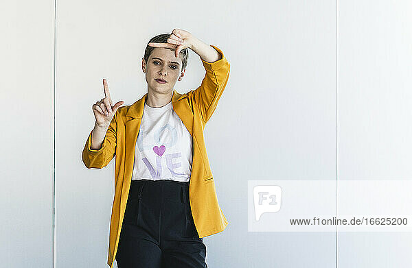 Businesswoman wearing yellow blazer making finger frame while standing against wall in office