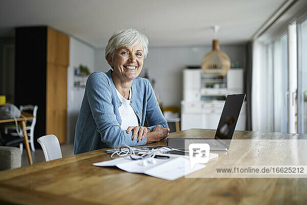 Senior woman sitting with arms crossed at home