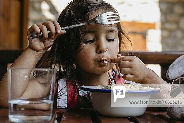Mädchen isst Essen  während sie zu Hause am Tisch sitzt Mädchen isst Essen, während sie zu Hause am Tisch sitzt