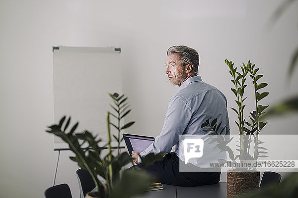Businessman using laptop while sitting on table at office