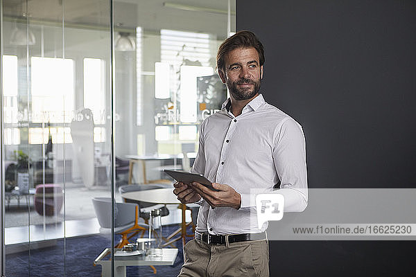 Businessman holding digital tablet while leaning on wall at office