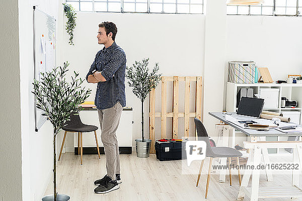 Man with arms crossed planning while standing at office