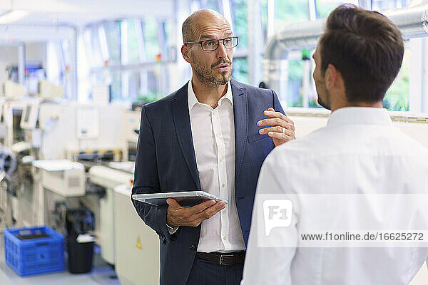 Confident businessman discussing with young male colleague while holding digital tablet at factory