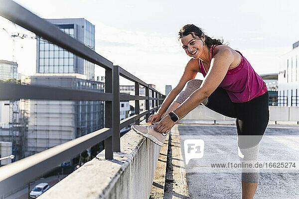 Smiling young woman tying shoelace on railing against sky