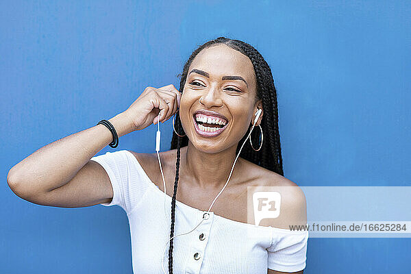 Cheerful woman listening music while standing against blue wall