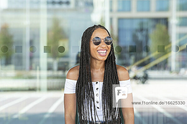 Beautiful woman wearing sunglasses while standing against glass wall in city