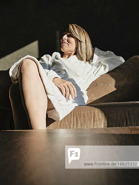 Lächelnde ältere Frau  die wegschaut  während sie sich auf dem Sofa im Hotel entspannt Lächelnde ältere Frau, die wegschaut, während sie sich auf dem Sofa im Hotel entspannt