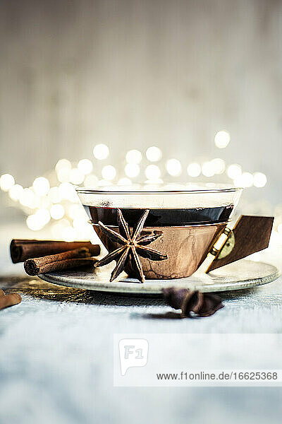 Cup of mulled wine with cinnamon sticks and star anise